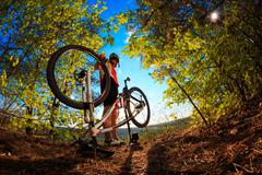 Man cyclist repairing a bike  against blue sky Stock Photos