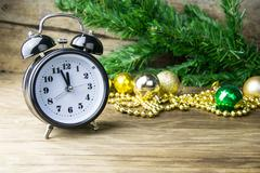 Alalrm-clock and Christmas baubles on wooden background Stock Photos