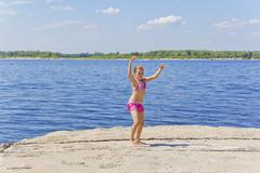 Cute girl on the riverbank in pink swimsuit - stock photo