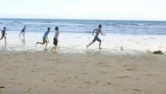 Playing football children on beach. Kids enjoy sport on sand in slow motion. Stock Footage