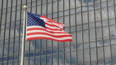 American flag in front of office building. Slow zoom and hold. - stock footage