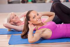 Pretty fit girls are exercising in gym - stock photo
