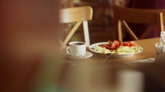 Girl carries her breakfast at the table Stock Footage