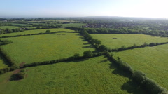 4K Aerial flight above forest, fields & housing in the English countryside Stock Footage