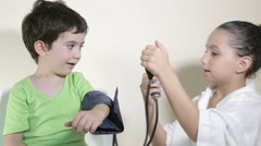 Kids play doctor and measure blood pressure Stock Footage