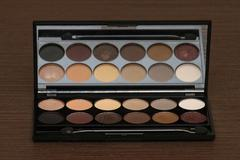 Neutral eye shadows palette with applicator and large mirror - stock photo
