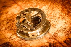 Vintage compass lies on an ancient world map. - stock photo