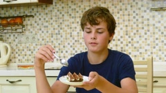 Happy teenager eating for dessert at the dining table Stock Footage