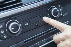 Finger pushing the air conditioner button Stock Photos