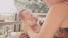 A newborn baby yawns while her mother holds her Stock Footage