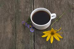 Three blue flowers, one yellow and a cup of coffee on a wooden table Stock Photos