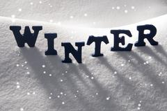 Stock Photo of Blue Word Winter On Snow, Snowflakes