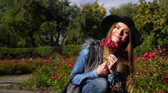 Woman smelling red rose flowers in park 4K - stock footage