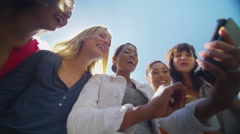 4K Happy attractive female friends looking at mobile phone outdoors  Stock Footage