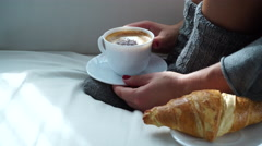 Stock Video Footage of Woman sitting with coffee cup and croissant on couch 4K