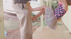 A little girl wearing a tutu climbs up her dad after he gets home from work - stock footage