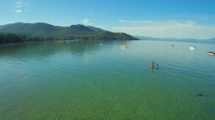 An aerial shot of a woman and her dog paddle boarding on Lake Tahoe. - stock footage