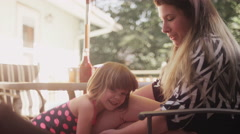 A mom bounces her daughter up and down on her leg Stock Footage