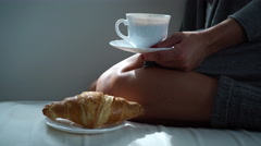 Woman sitting with coffee cup and croissant on couch 4K - stock footage