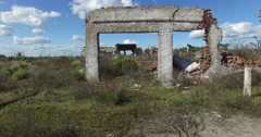 Going through the frame of a destroyed doors house. Sad urban landscape. - stock footage
