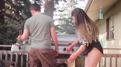 A husband and wife on their porch barbecuing and petting their dog Stock Footage