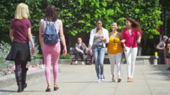 4K Happy attractive female friends chatting as they walk through city Stock Footage