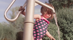 A little girl pumping water out of a faucet at a park Stock Footage