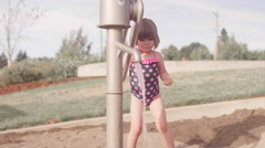 A little girl pumping water out of a faucet at a park with sand - stock footage