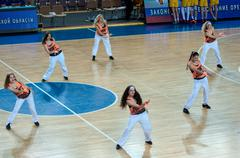 Stock Photo of Girls cheerleading appear on basketball parquet