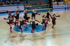 Girls cheerleading appear on basketball parquet Stock Photos