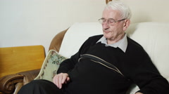 4K Elderly man sitting alone at home, changing tv channels with remote control - stock footage