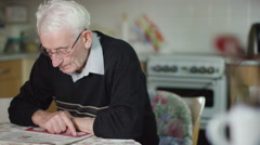4K Elderly man sitting alone reading newspaper at home Stock Footage