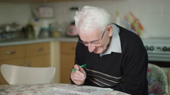 4K Elderly man sitting alone doing a crossword puzzle in the newspaper - stock footage