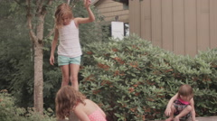 Three sisters play on a short wall in a park Stock Footage