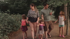 A family walking down a park trail while holding hands - stock footage