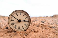 Stock Photo of Classic Analog Clock In The Sand