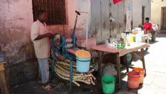 Vendor extracting juice from sugarcane, Stone Town, Zanzibar, Tanzania Stock Footage