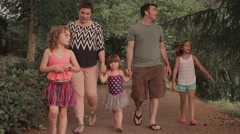 A family walking down a park trail Stock Footage