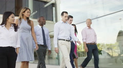 4K Mixed ethnicity business team walking together outside office building Stock Footage