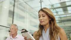 4K Attractive businesswoman looking at mobile phone as she walks outside office Stock Footage
