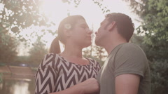 A romantic couple kisses next to a lake - stock footage