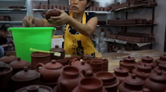 Female workers are polishing and cleaning the pottery tea pot - stock footage