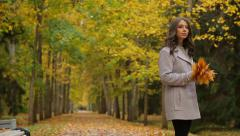 Pretty woman with maple golden leaves waiting for someone in a autumn park. - stock footage