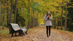 Stock Video Footage of Pretty woman with maple golden leaves waiting for someone in a autumn park.