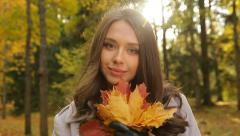 Stock Video Footage of Portrait of a pretty woman with maple golden leaves in an autumn park at sunset.