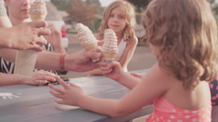 A father hands out ice cream cones to his kids at a picnic table - stock footage