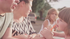 A father shares his drink with his daughter at a picnic table - stock footage