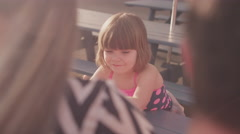 A girl wipes ice cream on her sister's nose at a picnic table - stock footage