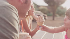 A father and daughter share their ice cream at a picnic table Stock Footage