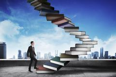 Stock Photo of Business person step up flying book that look like stair